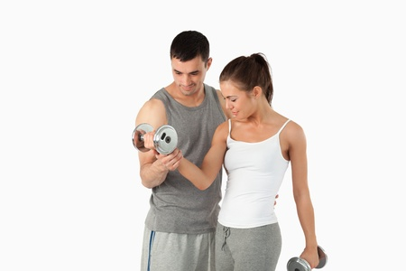 Man helping a woman to work out against a white background Stock Photo - 11624661