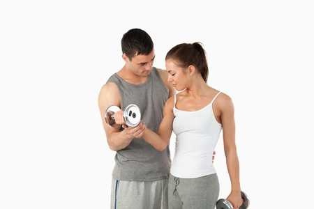 trabalhar fora: Man helping a young woman to work out against a white background