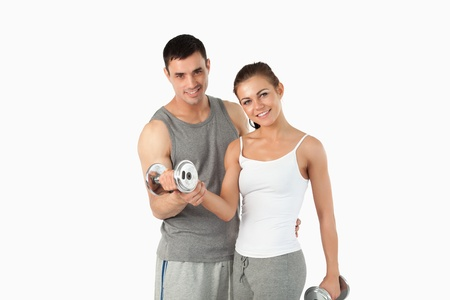 Man helping a gorgeous woman to work out against a white background photo