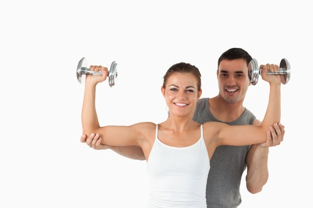 trabalhar fora: Young man helping a smiling woman to work out against a white background