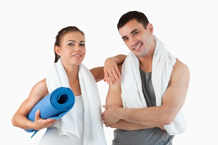 Fit couple going to practice yoga against a white background photo