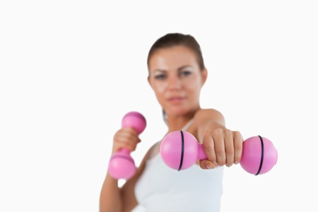 Healthy woman working out with dumbbells against a white background Stock Photo - 11623779