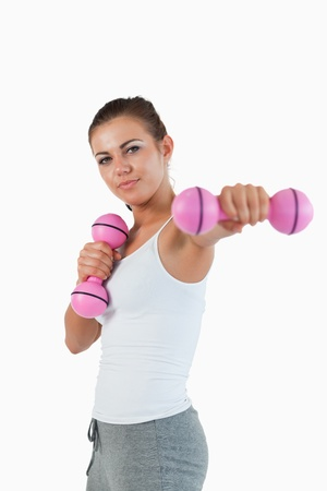 Portrait of a beautiful woman working out with dumbbells against a white background photo