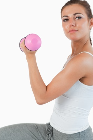 Close up of a woman working out with dumbbells against a white background photo
