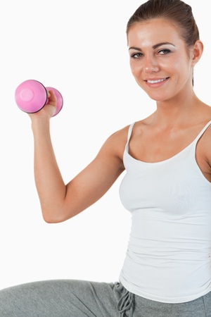 Close up of a young woman working out with dumbbells against a white background photo