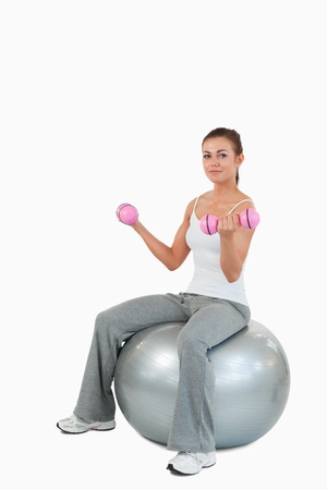 Portrait of a woman working out with dumbbells and a ball against a white background photo