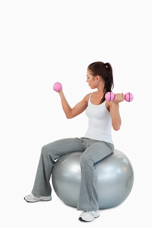 Portrait of a young woman working out with dumbbells and a ball against a white background photo