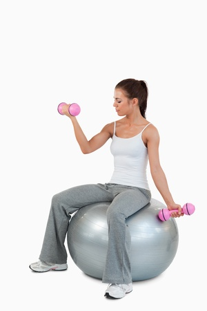 Portrait of a cute woman working out with dumbbells and a ball against a white background photo