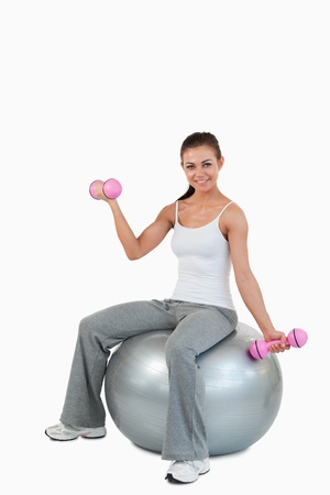 Portrait of a smiling woman working out with dumbbells and a ball against a white background photo