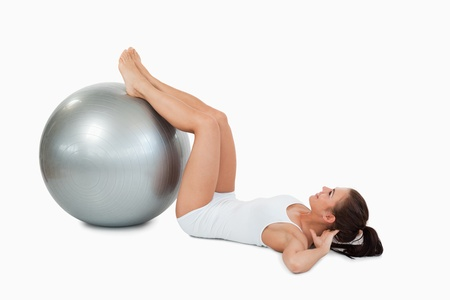 balance ball: Woman developing  her abs with a ball against a white background