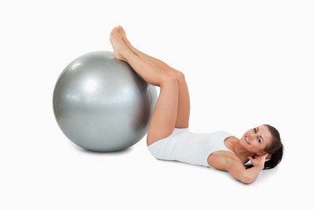 Young woman developing her abs with a ball against a white background Stock Photo - 11623971