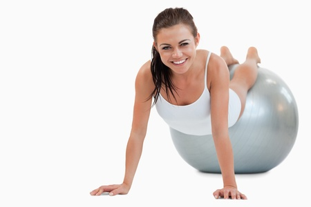 Smiling woman working out with a ball against a white background photo