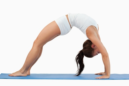 Woman practicing gymnastic against a white background photo