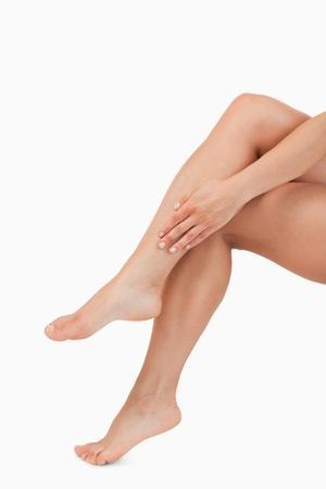 pies bonitos: Retrato de una mano que toca las piernas sobre un fondo blanco