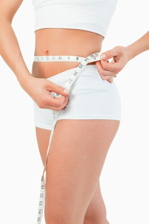 weight loss woman: Portrait of a woman using a measuring tape against a white background