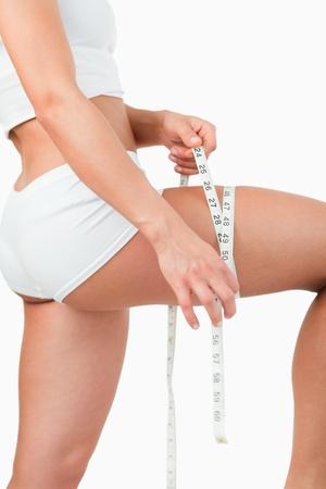muslos: Retrato de una mujer mide su muslo contra un fondo blanco