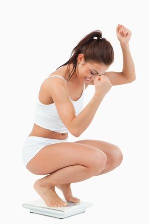 dieting: Portret van een gelukkige vrouw gehurkt op schalen tegen een witte achtergrond