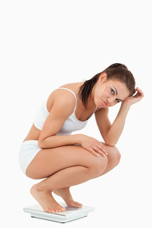Portrait of an unhappy woman squatting on scales against a white background photo