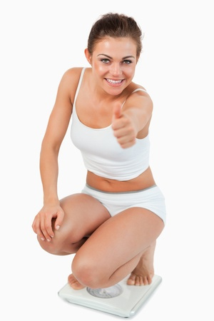 Portrait of a woman squatting on scales with the thumb up against a white background photo