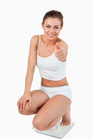 Portrait of a thin woman squatting on scales with the thumb up against a white background photo