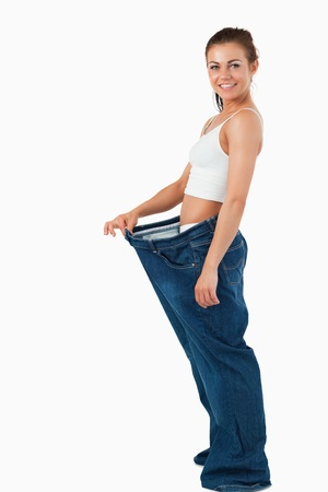 lose: Portrait of a woman wearing too large pants against a white background Stock Photo