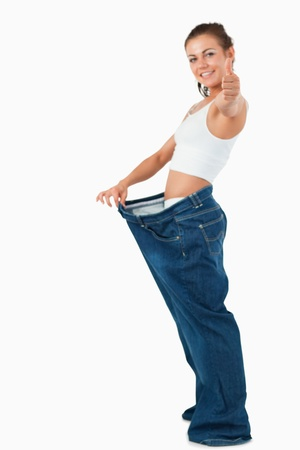 Portrait of a fit woman wearing too large pants with the thumb up against a white background photo