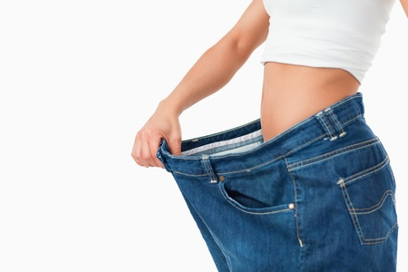 Woman wearing too large pants against a white background