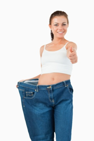 Portrait of a woman wearing too large jeans with the thumb up against a white background photo