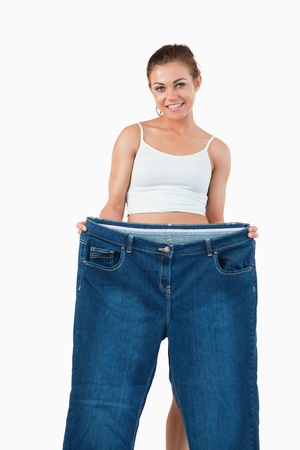 Portrait of a woman showing large jeans against a white background photo