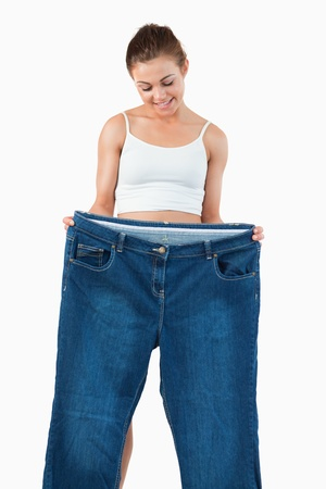 Portrait of a fit woman showing large jeans against a white background photo