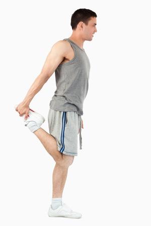 Retrato de un hombre de los deportes de estiramiento en la pierna contra un fondo blanco