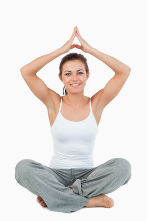 Portrait of a woman in a meditation position against a white background photo