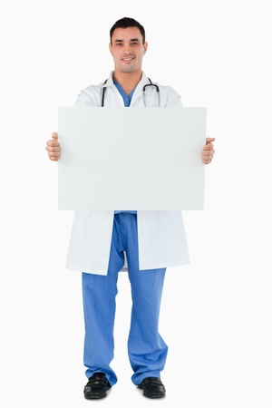 Portrait of a young doctor holding a blank panel against a white background photo