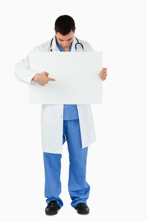 Portrait of a young doctor pointing at a blank panel against a white background Stock Photo - 11623781