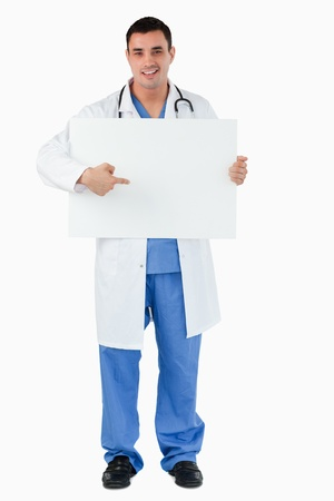 Portrait of a handsome doctor pointing at a blank panel against a blank panel Stock Photo - 11623805