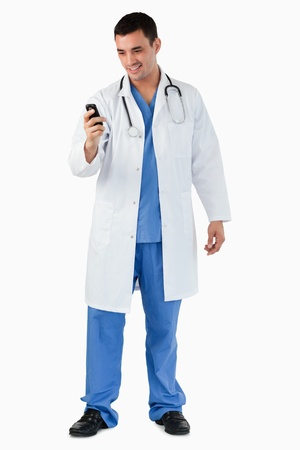 Portrait of a doctor dialing on his mobile phone against a white background photo