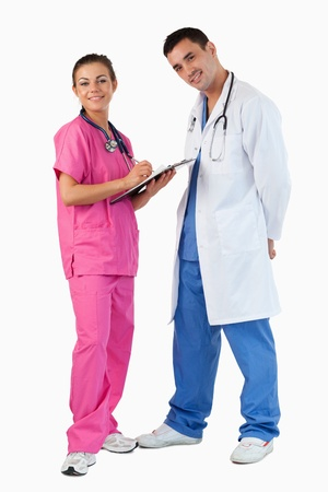 Portrait of a doctor talking while a nurse is taking notes against a white background Stock Photo - 11636995