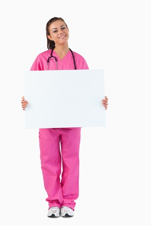 Portrait of a female doctor holding a blank panel against a white background photo
