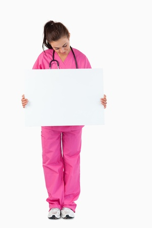 Portrait of a brunette doctor holding a blank panel against a white background photo
