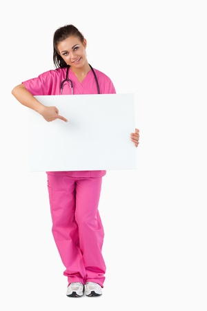 Portrait of a brunette doctor pointing at a blank panel against a white background photo