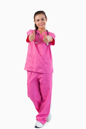 Portrait of a female doctor with thumbs up against a white background Stock Photo - 11624009