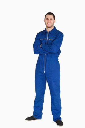 boiler suit: Smiling young mechanic in boiler suit with arms folded against a white background Stock Photo
