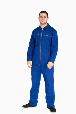 studio happy overall: Smiling young mechanic in boiler suit against a white background