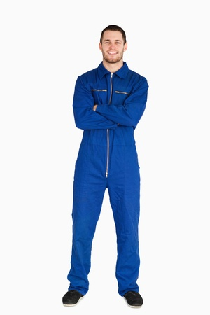 studio happy overall: Smiling mechanic in boiler suit against a white background