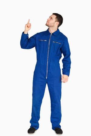 boiler suit: Young mechanic in boiler suit pointing up against a white background