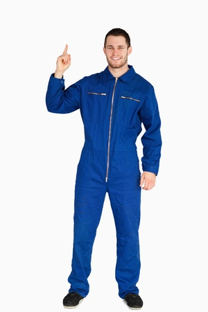 boiler suit: Smiling young mechanic in boiler suit pointing up against a white background