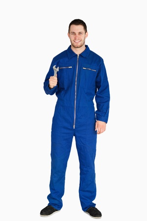 boiler suit: Smiling young mechanic in boiler suit with a wrench against a white background