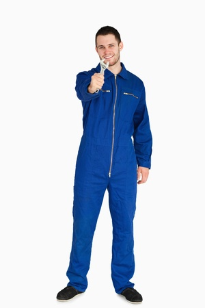 boiler suit: Smiling young mechanic in boiler suit presenting his wrench against a white background Stock Photo