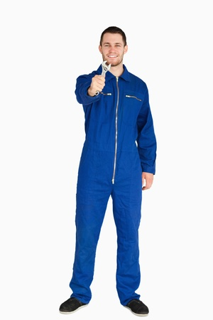 Smiling young mechanic in boiler suit showing his wrench against a white background photo
