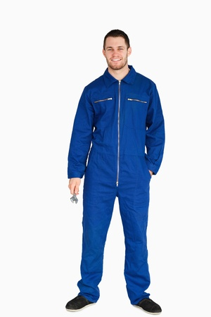 boiler suit: Smiling young mechanic in boiler suit holding a wrench against a white background